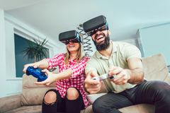 Amis heureux jouant des jeux vidéo avec des verres de réalité virtuelle Image stock