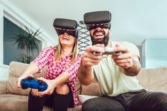 Amis heureux jouant des jeux vidéo avec des verres de réalité virtuelle Photo stock