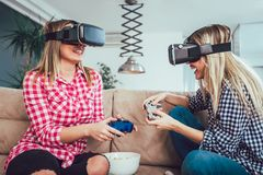 Amis heureux jouant des jeux vidéo avec des verres de réalité virtuelle Photographie stock