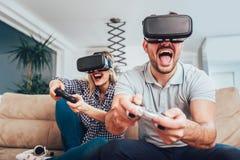 Amis heureux jouant des jeux vidéo avec des verres de réalité virtuelle Photo libre de droits
