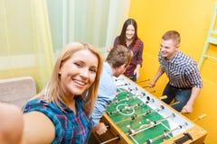 Amis heureux jouant l'hockey de table Photographie stock libre de droits