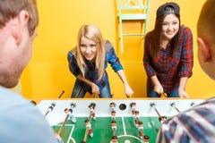 Amis heureux jouant l'hockey de table Images stock