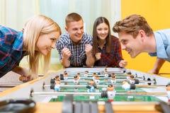 Amis heureux jouant l'hockey de table Photos libres de droits