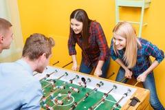 Amis heureux jouant l'hockey de table Image stock