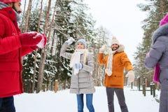 Amis heureux jouant la boule de neige dans la forêt d'hiver Photos libres de droits