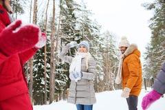 Amis heureux jouant la boule de neige dans la forêt d'hiver Photos stock