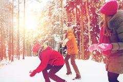 Amis heureux jouant la boule de neige dans la forêt d'hiver Image libre de droits