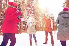 Amis heureux jouant la boule de neige dans la forêt d'hiver Photographie stock libre de droits
