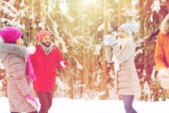 Amis heureux jouant la boule de neige dans la forêt d'hiver Images stock