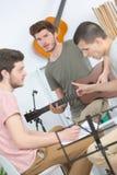 Amis heureux jouant la guitare et écoutant la musique à la maison Photo stock