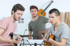 Amis heureux jouant la guitare et écoutant la musique à la maison Image libre de droits