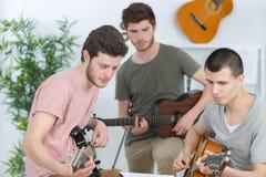 Amis heureux jouant la maison de guitarat Image libre de droits