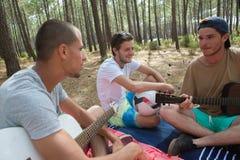 Amis heureux jouant la musique dans la forêt Photo stock
