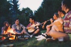 Amis heureux jouant la musique et appréciant le feu Photographie stock