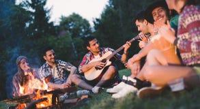 Amis heureux jouant la musique et appréciant le feu Photos stock