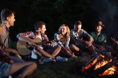 Amis heureux jouant la musique et appréciant le feu Photos libres de droits