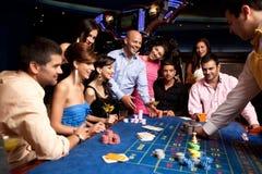 Amis heureux jouant la roulette dans un casino Photographie stock libre de droits