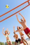 Amis heureux jouant la volée de plage Photos libres de droits