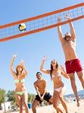 Amis heureux jouant la volée de plage Photo libre de droits