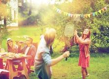 Amis heureux jouant le badminton au jardin d'été Photographie stock libre de droits