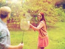 Amis heureux jouant le badminton au jardin d'été Photos stock