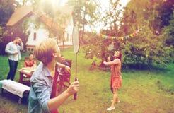 Amis heureux jouant le badminton au jardin d'été Photographie stock