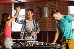 Amis heureux jouant le football de table Image libre de droits