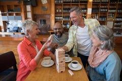 Amis heureux jouant le jeu de jenga tout en ayant la tasse de café Photo libre de droits