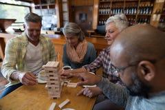 Amis heureux jouant le jeu de jenga tout en ayant la tasse de café Photographie stock