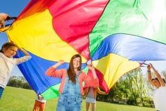 Amis heureux jouant le parachute d'arc-en-ciel en été Photo libre de droits