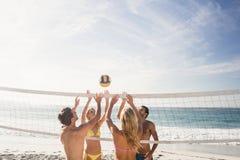 Amis heureux jouant le volleyball de plage Photos libres de droits
