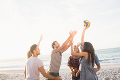 Amis heureux jouant le volleyball de plage Image stock