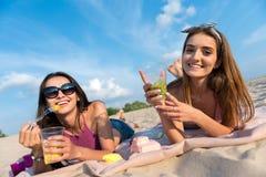Amis heureux joyeux se reposant sur le sable Images stock