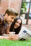 Amis heureux lisant le journal sur la pelouse Photographie stock libre de droits