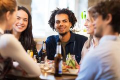 Amis heureux mangeant à la barre ou au restaurant Photos stock