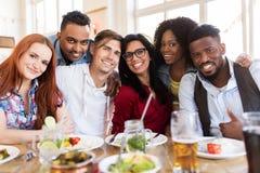 Amis heureux mangeant au restaurant Photos libres de droits