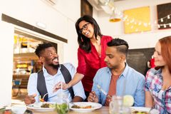 Amis heureux mangeant au restaurant Image stock