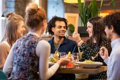 Amis heureux mangeant au restaurant Photographie stock libre de droits