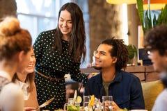 Amis heureux mangeant au restaurant Images stock