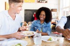 Amis heureux mangeant au restaurant Image libre de droits