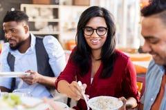 Amis heureux mangeant au restaurant Photographie stock