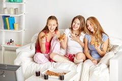 Amis heureux mangeant de la pizza et regardant la TV à la maison Photographie stock libre de droits