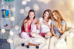 Amis heureux mangeant de la pizza et regardant la TV à la maison Images stock