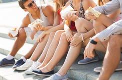 Amis heureux mangeant des aliments de préparation rapide à emporter dans la ville Photographie stock
