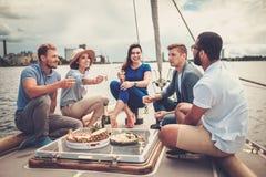 Amis heureux mangeant des fruits et buvant sur un yacht Photographie stock libre de droits