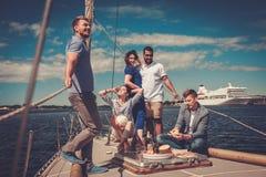 Amis heureux mangeant des fruits et buvant sur un yacht Photo libre de droits