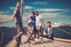 Amis heureux mangeant des fruits et buvant sur un yacht Photos libres de droits