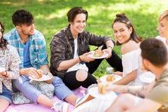 Amis heureux mangeant des sandwichs au pique-nique d'été Image stock