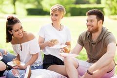 Amis heureux mangeant des sandwichs au pique-nique d'été Photographie stock