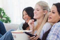 Amis heureux mangeant du maïs éclaté et regardant la TV Image libre de droits